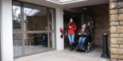 une-personne-en-fauteuil-sortn-de-chez-elle-avec-auxiliaire-de-vie-660x330.png